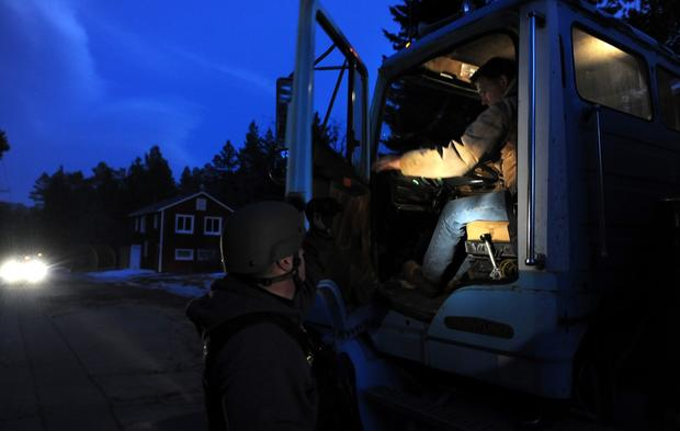 A police officer checks the cab of a truck along Switzerland Avenue in Big Bear Lake for shooting suspect Christopher Dorner.