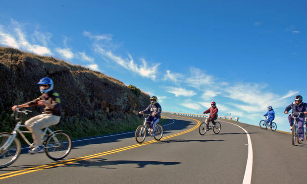 Riders cross back over the road after a scenic viewing stop on their sunrise bike trek down Haleakala, a nearly 10,000-foot volcano on Maui. Every year, thousands of bicyclists take the 27-mile ride to the sea.