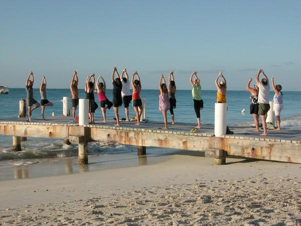 A yoga class with a view: Guests get in shape during a late afternoon workout at the edge of Grace Bay at Club Med's Turkoise resort on the Turks and Caicos Islands. Activities are included in the per-night rate guests are charged.