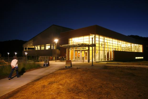 The glass panels of the Library Learning Center at Mendocino College in Ukiah glow at twilight. Many rural institutions are fighting to meet enrollment goals on which the state bases its funding.
