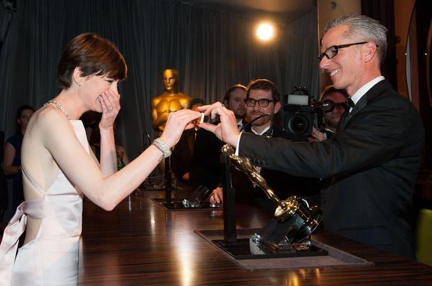 Supporting actress winner Anne Hathaway gets emotional while looking at her name on the engraved plate of her Oscar statue.