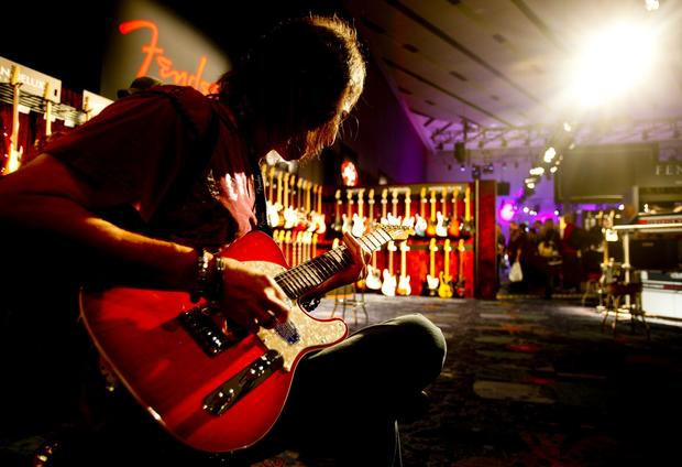Guitarist Hal Negin gets a little quiet time with one of the guitars in the Fender room.