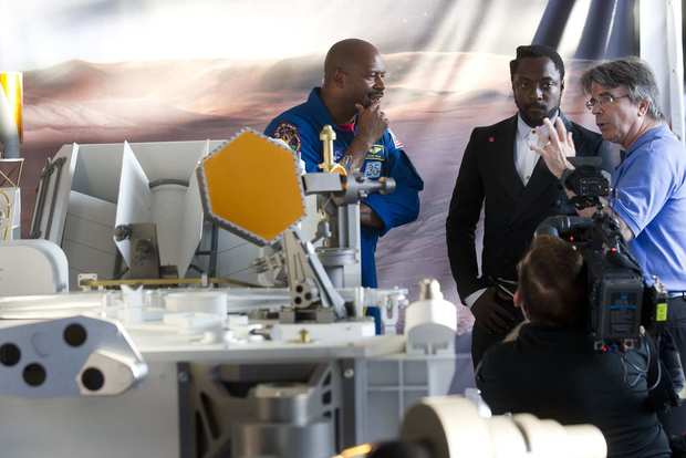 NASA scientist Jim Garvin, right, talks with musician will.i.am, center, and astronaut Leland Melvin, left, next to a model of NASA's Mars Science Laboratory Curiosity rover at Jet Propulsion Laboratory in La Canada Flintridge.