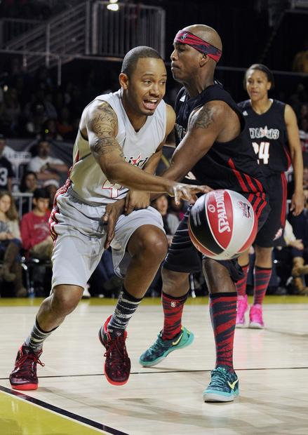 Television personality and model Terrence Jenkins drives past singer Ne-Yo in the second half of the celebrity game on Friday night in Houston.