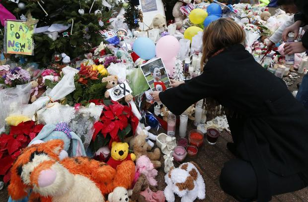 A woman puts a photo of a child on a makeshift memorial Monday in the Sandy Hook village of Newtown, Conn.