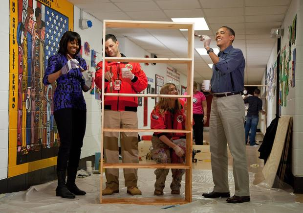 President Obama and First Lady Michelle Obama help Jeff Franco and Sheri Fisher paint a shelf at Burrville Elementary School in Washington.