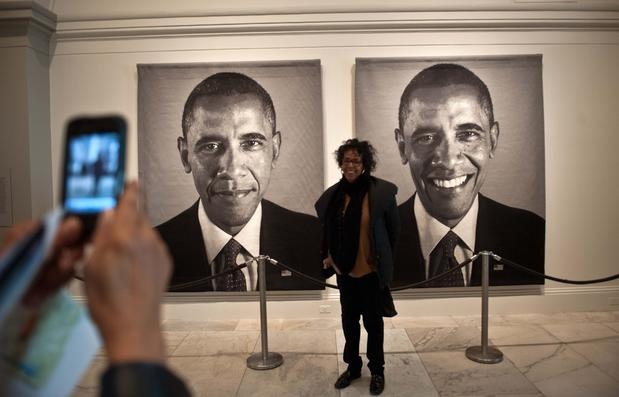 A visitor poses with a Chuck Close diptych of President Obama at the National Portrait Gallery in Washington.