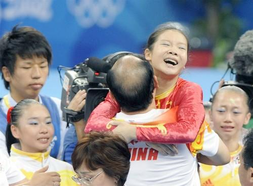 The Chinese team celebrates clinching the gold medal in the women's gymnastics team competition Wednesday in Beijing.