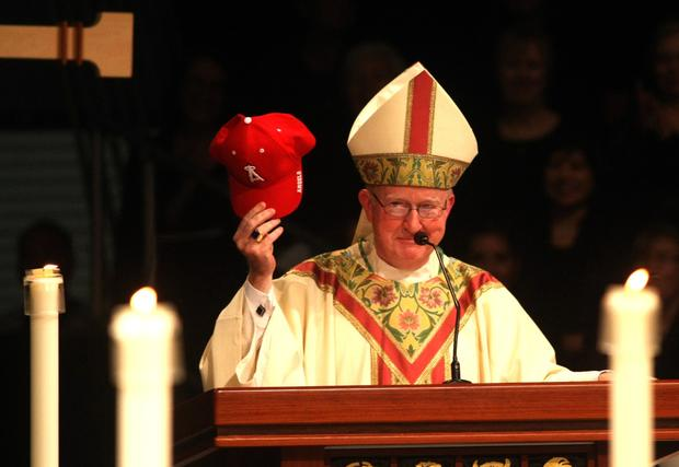 Bishop Kevin W. Vann, 61, holds up a Los Angeles Angels of Anaheim baseball cap during his speech to congregants at his installation as the new bishop of the Diocese of Orange.