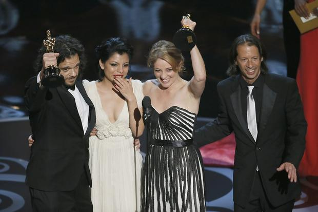 "Sean Fine and Andrea Nix Fine hold up their trophies after winning the Oscar for documentary short film for ""Inocente."" Between them is Inocente Izucar, the subject of the film, which records a young homeless woman's determination to be an artist."
