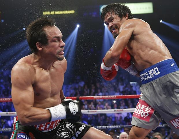 Juan Manuel Marquez is sent reeling by Manny Pacquiao during their welterweight fight at the MGM Grand Garden Arena.