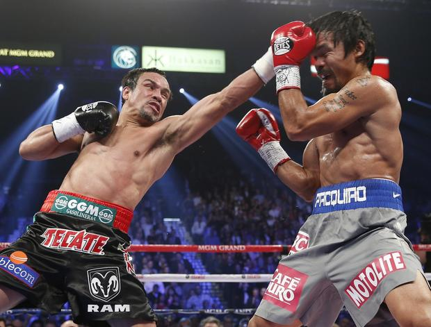 Juan Manuel Marquez lands a left jab against Manny Pacquiao in their welterweight fight in Las Vegas in December. Marquez's upcoming fight against Timothy Bradley, now set for Oct. 12, pits the last two men to beat Pacquiao -- Marquez by knockout and Bradley by dubious decision last summer.