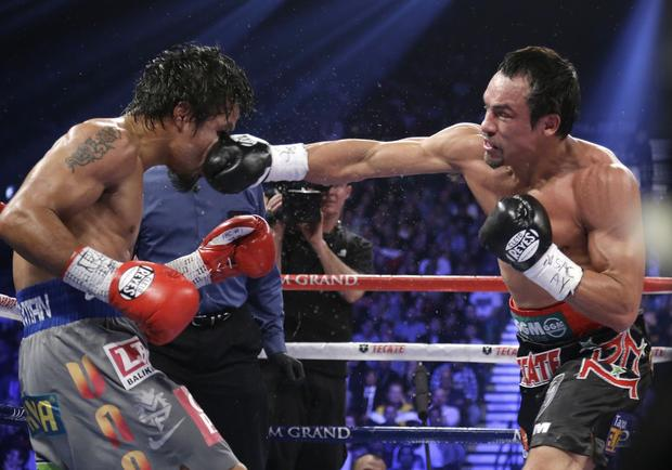 Juan Manuel Marquez delivers a blow to the face of Manny Pacquiao in their WBO welterweight bout in Las Vegas.