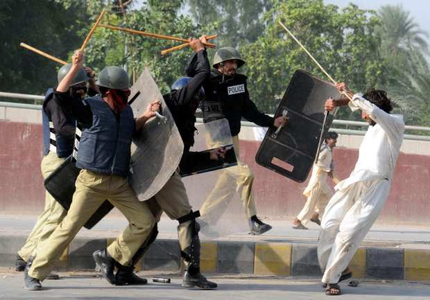 "Riot police in Peshawar descend upon protesters with batons during a demonstration protesting the anti-Islam movie ""Innocence of Muslims."" Violence erupted across Pakistan on Friday amid anger over the film."