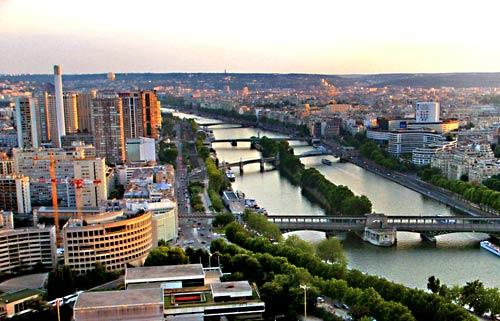 A view from the Eiffel Tower of Paris and the Seine River on a summer evening.