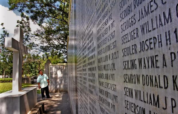 A visitor looks at names inscribed on the Capas National Shrine.