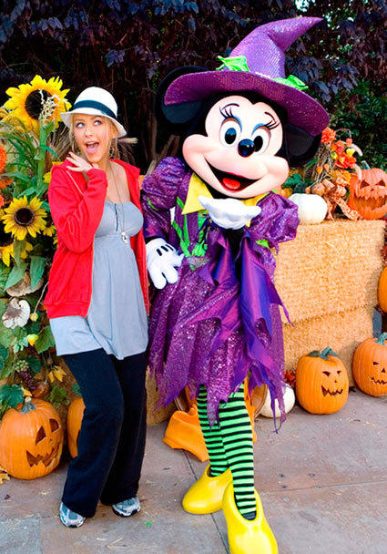 Former Mouseketeer and pop singer Christina Aguilera gets her scare on with a friendly Minnie Mouse witch during Halloween Time at Disneyland.