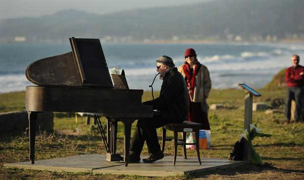 Artist Mauro Ffortissimo plays the piano for a crowd in Half Moon Bay. The piano has been perched overlooking the ocean, and city officials have given Ffortissimo until Thursday to remove it.
