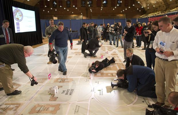 Photographers look at a model of the White House on a giant planning map during a media tour highlighting inaugural preparations being made by the Joint Task Force-National Capital Region for military and civilian planners.
