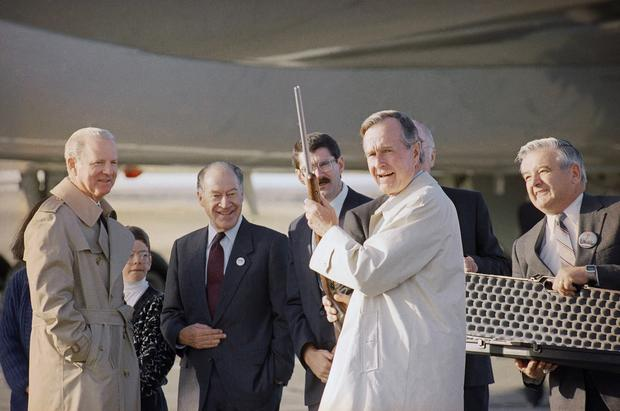 President George H.W. Bush displays a rifle given to him as a gift, in Billings, Mont., as his Chief of Staff James Baker, left, watches during a campaign stop in 1992.