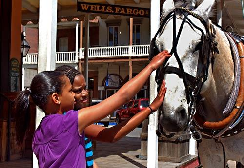 Outside the Wells Fargo Museum in Old Sacramento, where Pony Express riders finished their westbound journeys in 1860-61, two young visitors from Vacaville, Calif., Shateema Harrison, left  and Kelis Atkins, both 10 years old, get acquainted with a carriage horse.