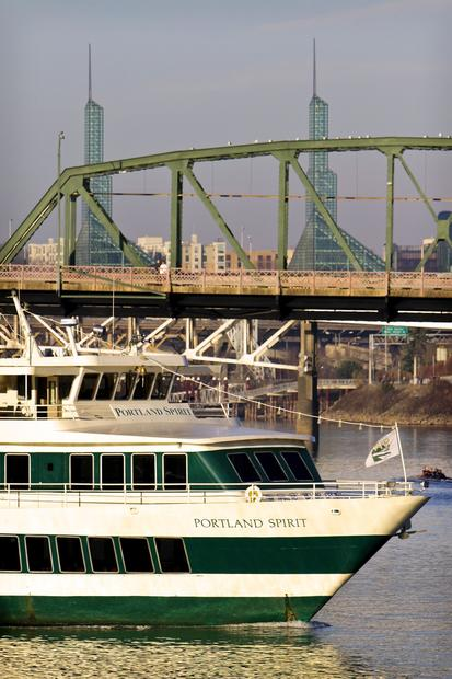 The Portland Spirit cruises the Willamette River with Hawthorne Bridge in the background.