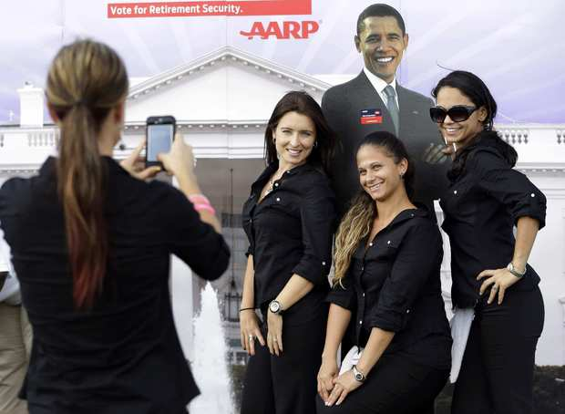 Workers pose for a photo with a life-sized cutout of President Obama at Lynn University.