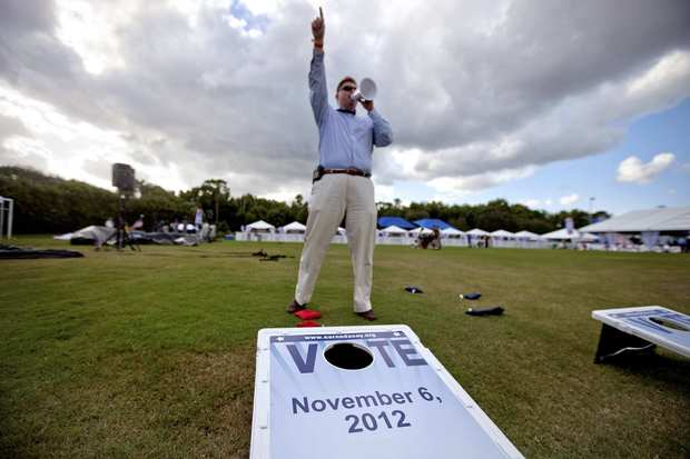AARP staff member Pete Jeffries calls for entrants at a debate party to take part in a game of bean bag toss.