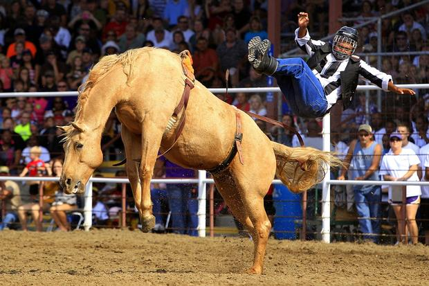 An inmate is thrown from a bronco while participating in the bareback riding competition during the prison rodeo held at the Louisiana State Penitentiary.