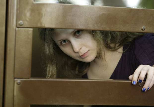 "Maria Alyokhina, member of a Russian feminist punk group, appears behind bars in a court in Moscow. She and two other band members are facing trial for performing a ""punk prayer"" against Vladimir Putin from a pulpit of a Moscow cathedral before Russia's presidential election in March, in which Putin won a third term."