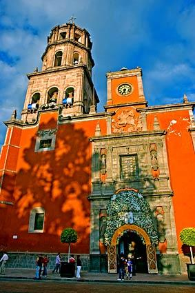 The orange Church of San Francisco features a bell tower and an ornate entrance. The city's historic center is full of colonial buildings.