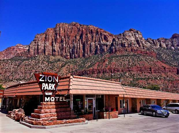 Towering red sandstone cliffs surround the low-slung Zion Park Motel in Springdale, Utah, built in 1972 and just a mile from the national park.