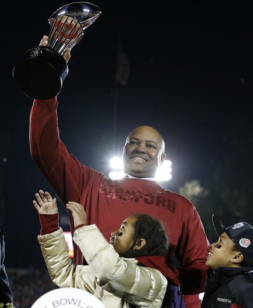 Stanford Coach David Shaw raises the Rose Bowl trophy next to his children after a 20-14 victory over Wisconsin in the Rose Bowl on Tuesday night in Pasadena.