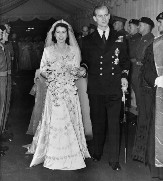 Queen Elizabeth and Prince Philip, Duke of Edinburgh, after their wedding. She wears a jeweled wedding gown and carries a  bouquet of orchids. Nov, 21, 1947.