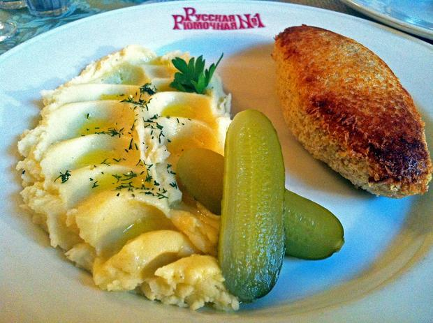 Rare Ladoga Lake fish cake is served with mashed potatoes and pickles at Russian Vodka Room No. 1 in St. Petersburg.