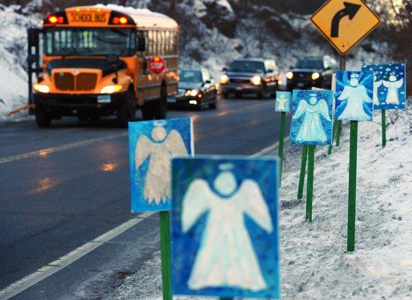 A school bus stops in front of 26 angels on the first day of classes since the shooting for Sandy Hook students.