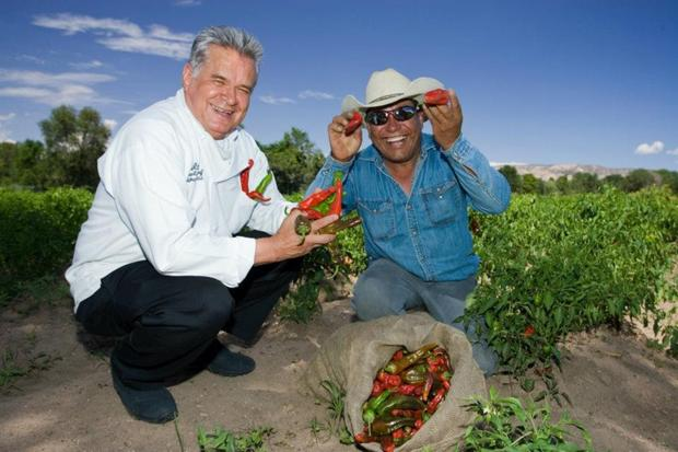 Executive chef Estevan Garcia and grower Chencho Ochoa show off freshly picked Chimayo chiles in a northern New Mexico farm field.