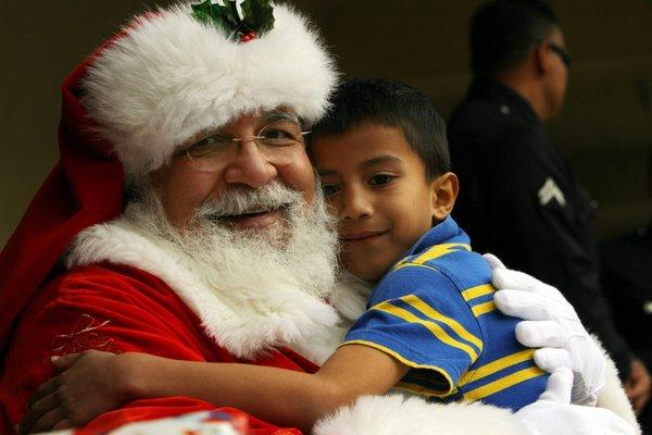 Santa Claus, a.k.a. David Fernandez, hugs Richard Fermen, 6, at Leo Politi Elementary School in Los Angeles.