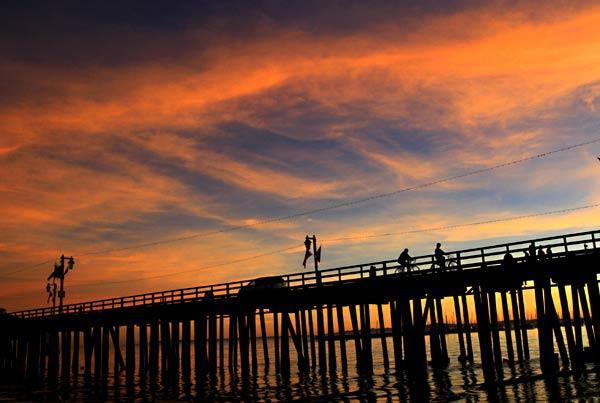 Cyclists ride on Stearns Wharf at sunset in Santa Barbara.