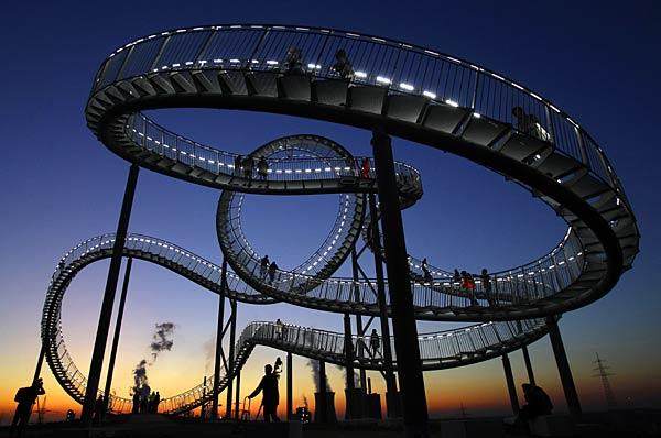 """Tiger and Turtle"" rises 68 feet high. Its base is 158 by 113 feet. The ""track"" stretches 722 feet and is about three feet wide."