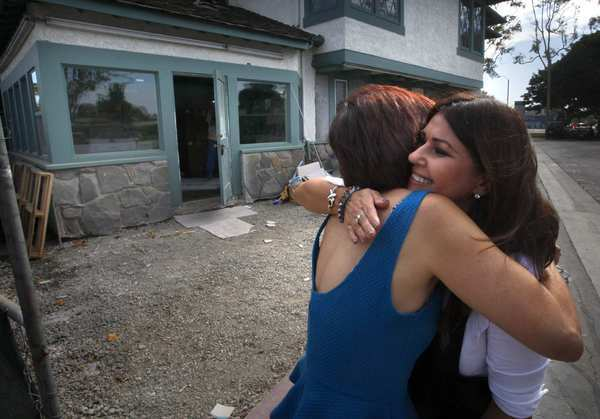 Irma Acosta, right, a survivor of last year's shooting attack at Salon Meritage and the shop's new owner, hugs designer Cynthia Pastor. The salon is being remodeled and is expected to reopen within weeks.