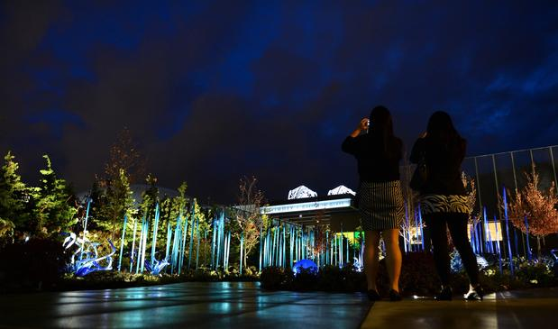 Visitors roam Chihuly Garden and Glass in the evening.