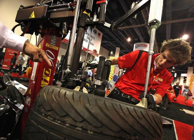 Caleb Ison demonstrates a tire and wheel mounting machine in the Corghi booth at the Las Vegas Convention Center during the SEMA Show.