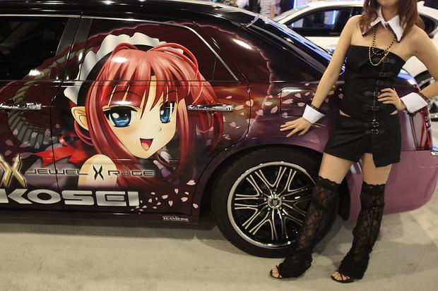 A model at the Kosei Racing Wheels booth stands by a car with an Anime cartoon at the Las Vegas Convention Center during the SEMA Show.