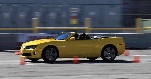Trade show participants drive a Chevy Camaro around a small track at the Las Vegas Convention Center for the SEMA Show.