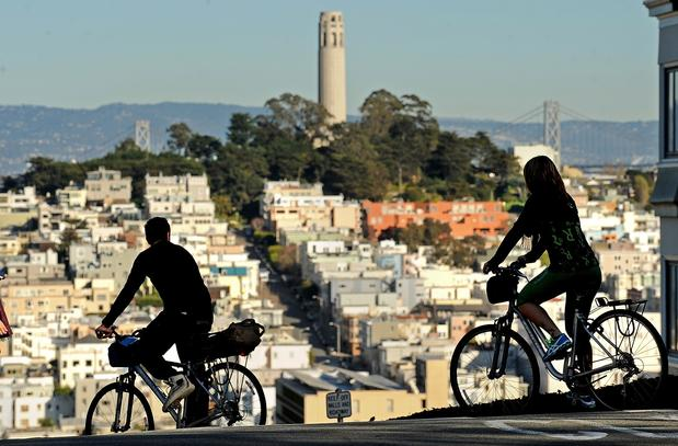 Coit Tower looms nearby as cyclists twist along Lombard Street.