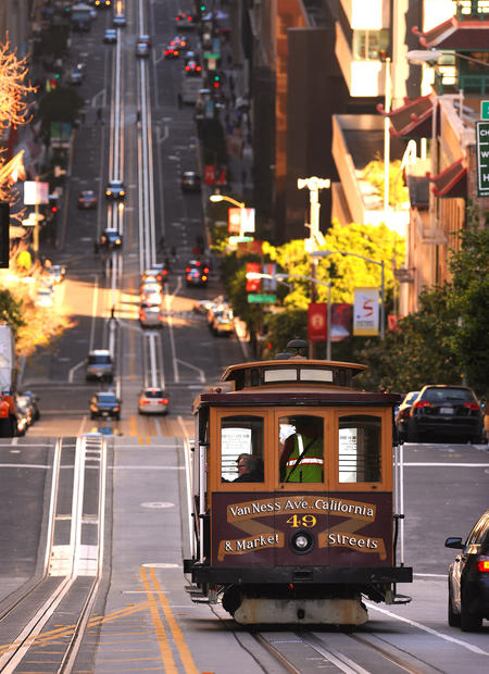 A cable car makes its way down California Street.