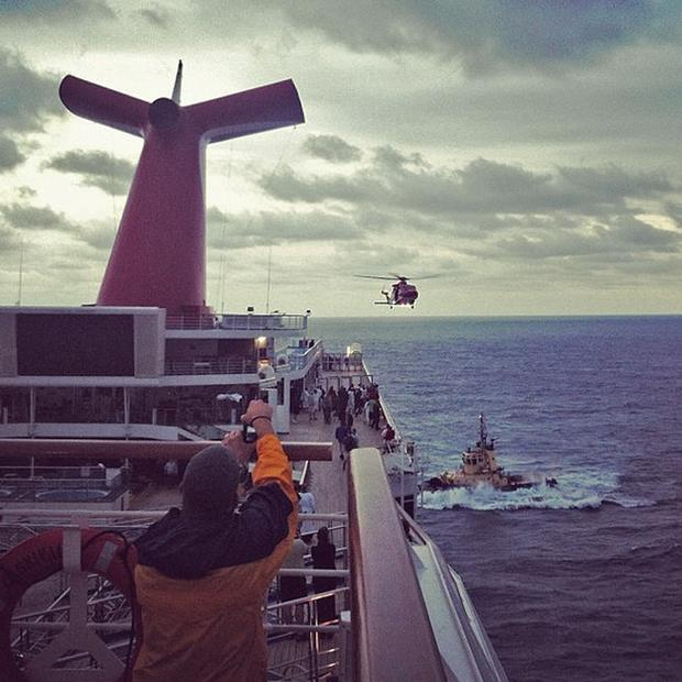 An Instagram photo provided by a passenger shows a Coast Guard helicopter flying over the Carnival cruise ship Triumph as it is towed toward Mobile, Ala., on Wednesday.