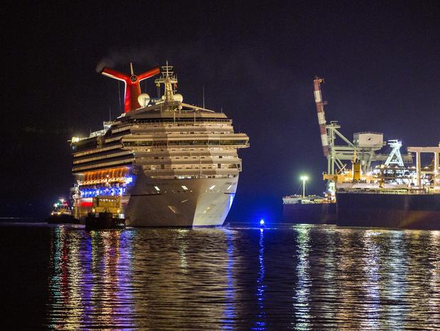 The crippled Carnival cruise ship Triumph limps into dock in Mobile, Ala.