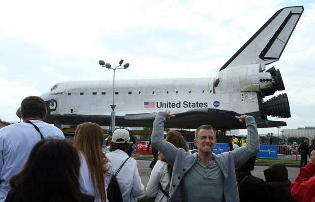Joseph Duffield of Venice appears to be holding up the space shuttle Endeavour as it sits in a parking lot in Westchester.